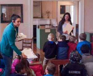 Shorter School of Education juniors Nancy Flores (left) and McKenna Massengill lead students through a historical literacy activity at Chieftains Museum.