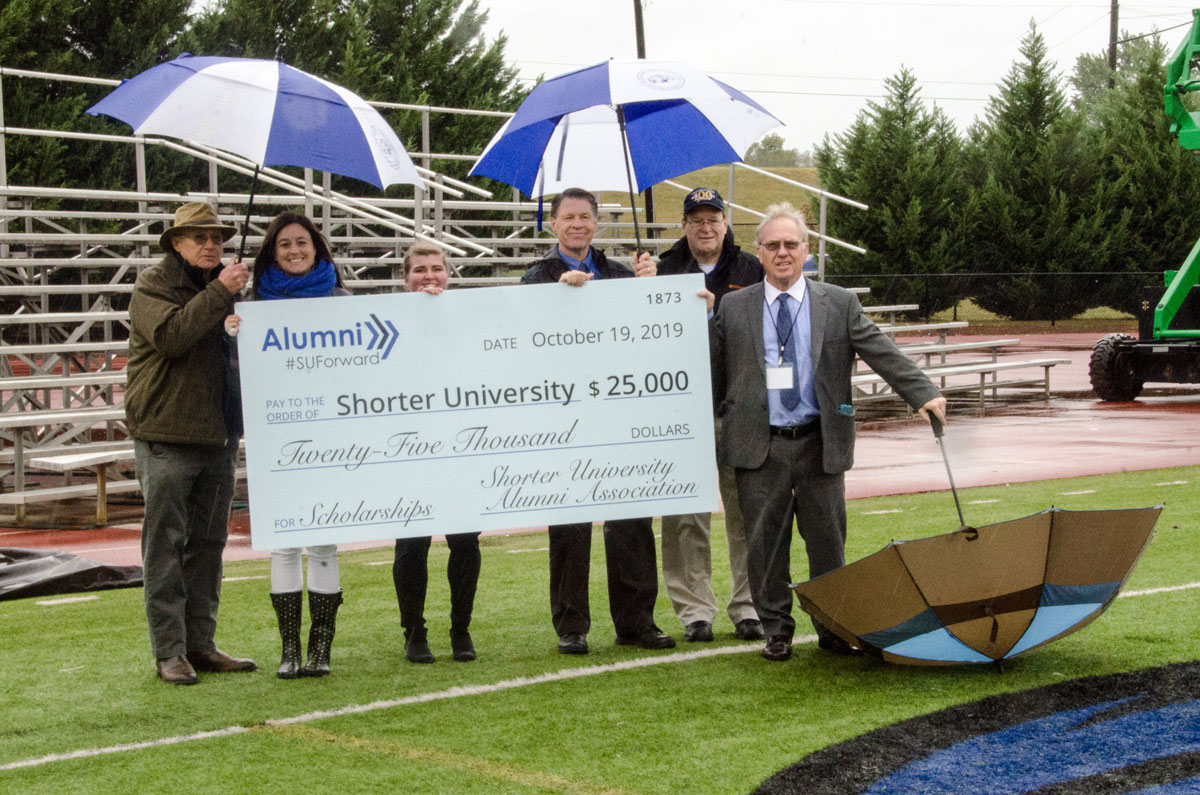 Alumni board members present check to Dr. Dowless