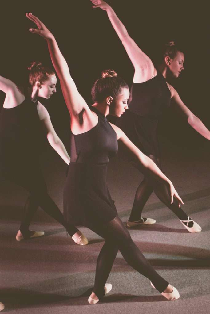 Three dancers in black dresses.