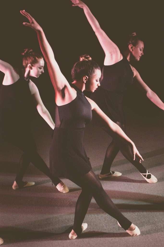 Three dancers in black dresses.