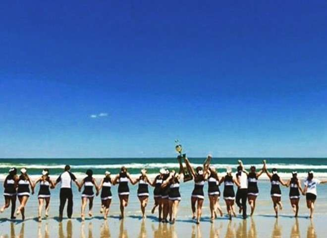 Cheerleading squad headed into ocean with trophy held high.