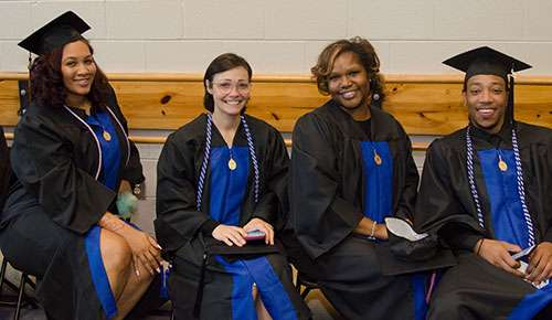 Four smiling graduates in caps and gowns.
