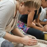 Students crafting bowls on a pottery wheel
