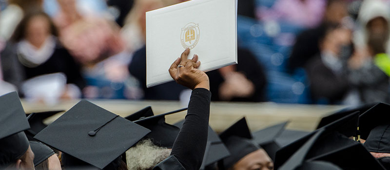 Graduate holding up a diploma