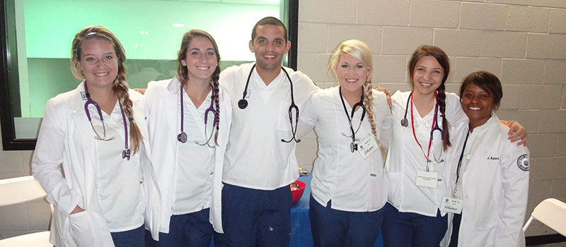 Six smiling Shorter nursing students in white lab coats