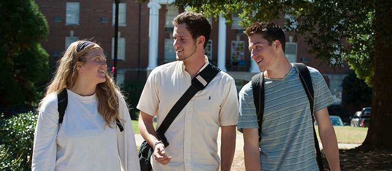 Three smiling students walking on campus