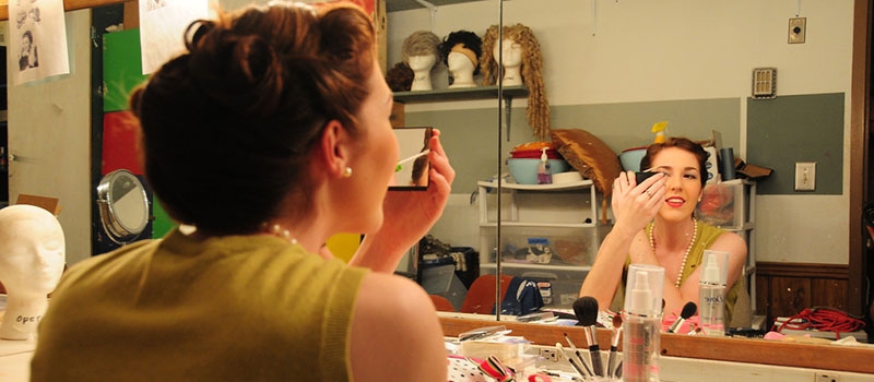 Theatre student putting on makeup in a mirror
