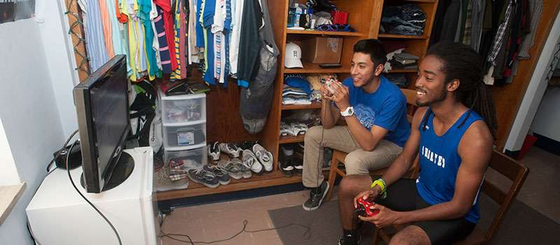 Two students playing video game in dorm room