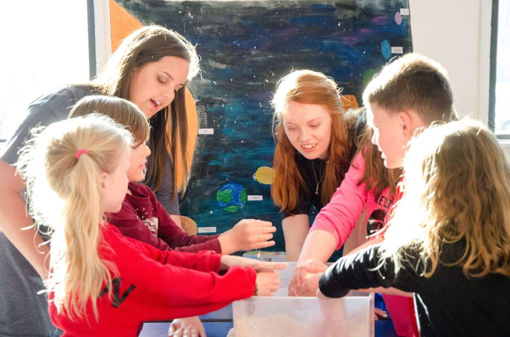 Shorter education majors let students at Pepperell Primary School play with Moon Sand while teaching about the solar system.