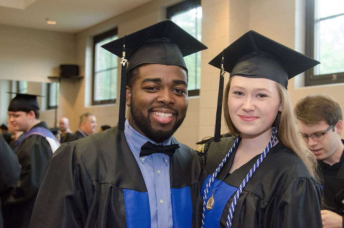 Two smiling graduates.