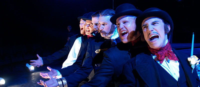 Scene from The Threepenny Opera / six men in black suits and bowler hats singing